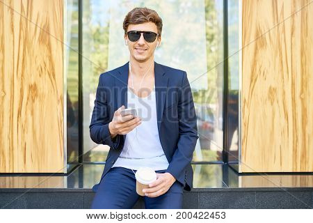 Portrait of handsome young man wearing sunglasses and trendy suit using smartphone outdoors while enjoying coffee break