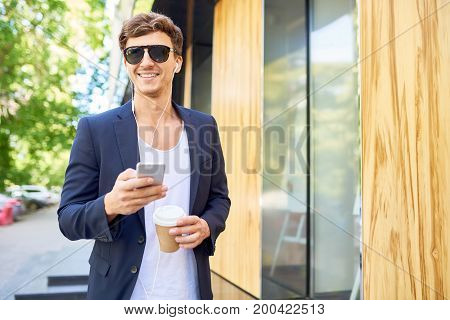 Portrait of handsome young man smiling happily while walking in city streets holding smartphone and paper coffee cup
