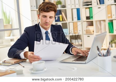 Portrait of successful young businessman working at desk in modern office, using laptop and reading documents