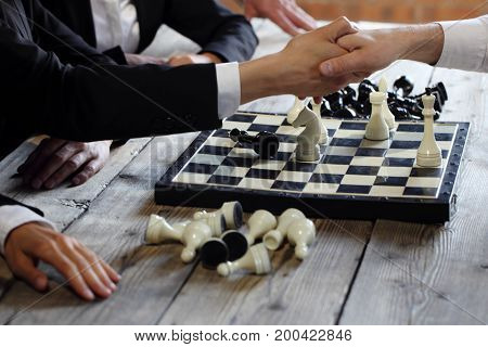 Business people shaking hands over chessboard after the game