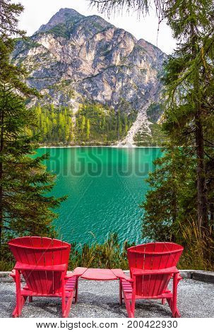 The concept of walking and eco-tourism. Two red deck chairs on the shore of the lake. Water reflects the surrounding forest and mountains