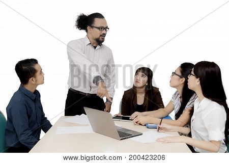 Afro businessman pointing at a laptop computer while scolding his colleague in the meeting isolated on wh