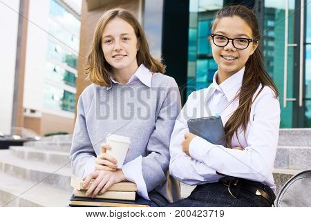 Cheerful pretty teenagers wearing school uniform looking at camera with toothy smiles while doing revision for exam at break, they holding textbooks in hands