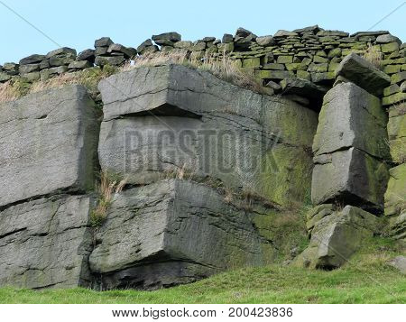 dramatic stone outcrop in yorkshire moors with craggy sandstone texture and drystone walling along the top