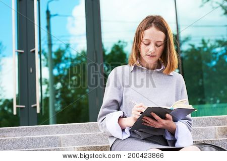 Portrait of concentrated teenager wearing uniform taking necessary notes while sitting on stairs of modern school building