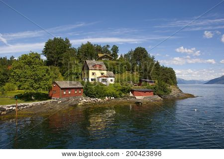 Idyllic landscape with wooden huts on Hardangerfjord