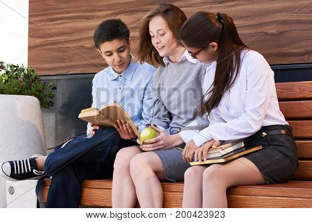 Group of teenage friends sitting together on park bench and reading interesting section of textbook, pretty girl wearing school uniform while their male friend in jeans and sneakers