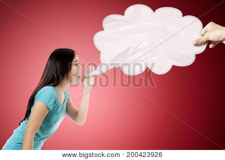 Photo of Asian woman saying something to an empty cloud shot with red background
