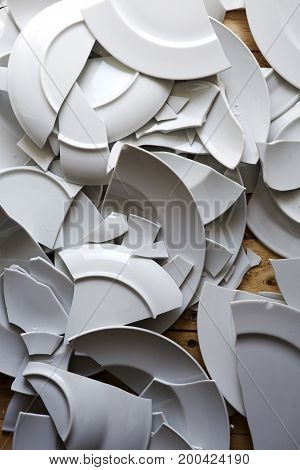 many white broken plates on a wooden floor
