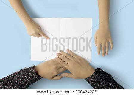 Hands of little boy showing a blank card while sitting with his father