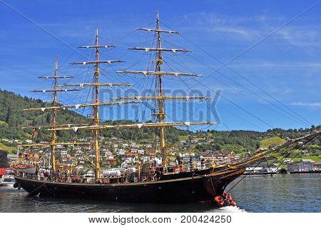 Norheimsund, Norway - July 2014: Old historic threemasted vessel in Norheimsund, Norway, with people onboard