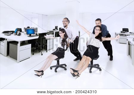 Image of two businessmen pushing their friends on the chair while racing in the workplace