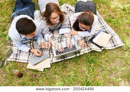 High angle view of concentrated secondary school students gathered together in green park and preparing for exams, piles of textbooks and laptop located on plaid