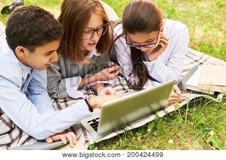 Concentrated teenage friends doing homework together with help of laptop while lying on lawn in sunny green park