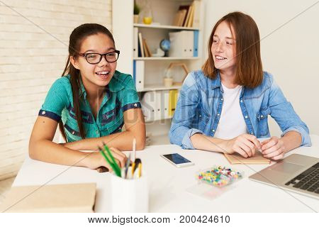 Cheerful teenage students wearing casual clothes sitting at school desk and chatting animatedly with each other at break time