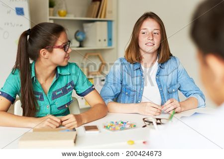 Freckled teenager sharing ideas with classmates concerning their joint school project while gathered together indoors