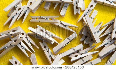 many wooden clothespin on a yellow background