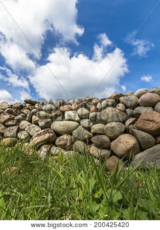 Old Stone wall buildt from the stones of the moraine Raet. With green grass in front and blue sky with clouds above, from Jomfruland, Norway. Vertical image