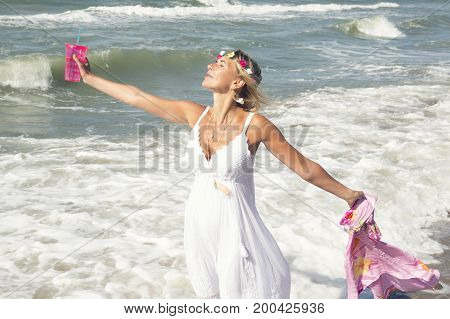 blond woman in white dress holding a cup and shawl and standing on the beach