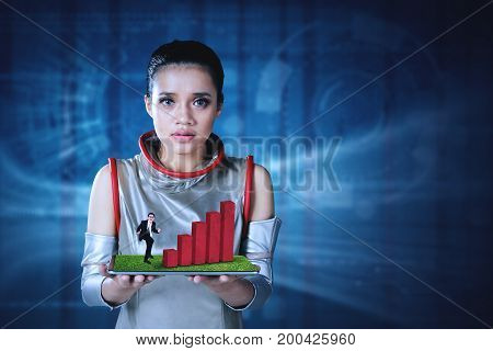 Futuristic woman showing a successful businessman with a growth chart on the digital tablet