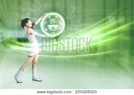 Picture of a futuristic young woman holding a virtual earth graphic save earth concept