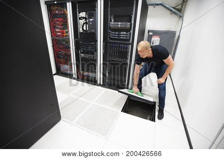 Full length of mid adult male computer engineer lifting floor tile using vacuum suction cups in datacenter
