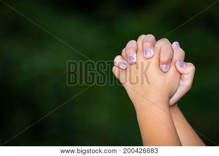 A young girl praying with clasped hands