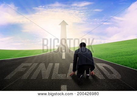 Young male manager kneeling on the road and ready to chase dream in the Finland country