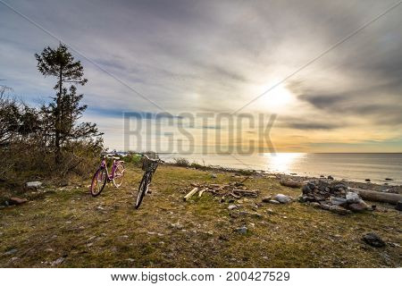 Two bikes standing at the grass at the beach. Ocean view from the pebble shore in the island of Jomfruland in Jomfruland National Park, Kragero, Norway. Jomfruland, meaning Virgin Land in Norwegian, is part of Raet, a big moraine from the ice age.