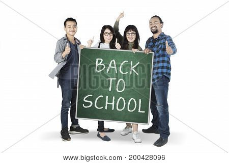 Multiracial students showing thumbs up while holding a chalkboard with text of back to school