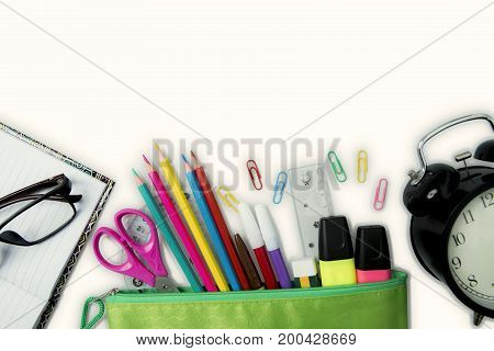 Top view of new school supplies with alarm clock isolated on white background