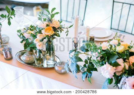 arrangement, vintage, style concept. on the table with peachy cloth there are numbers of silver shining candleholders of different forms and sizes, they are surrounded by flowers