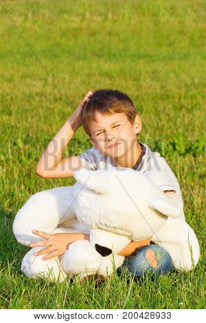 Boy sitting on the grass with teddy bear and planning or thinking about something