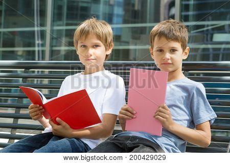 Children doing homework outdoors. Back to school concept.