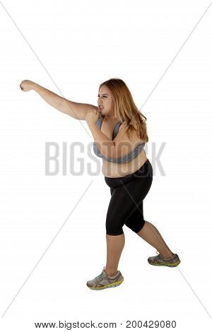 Young overweight woman wearing sportswear and punching something in the studio isolated on white background