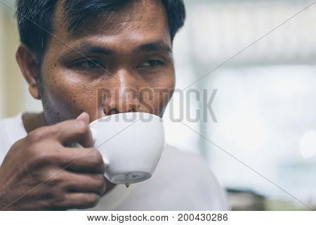 A man gestures surprise in taste of his late art in the coffee cup he was holding. Happy cofee taste concept.