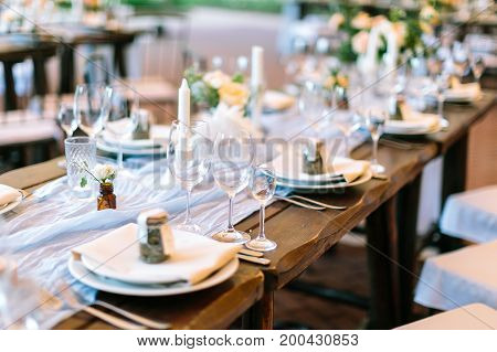 celebration, supper, restaurant business concept. oaken table covered with white tableware lying in center and served for starting banquet and decorated with beautiful small bunches and transparent