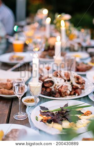 comfort, food, setting concept. dining table for celebrating holidays in the wild, there is silverware, dishes full of delicious meal, glasses with water and candles for cosy atmosphere
