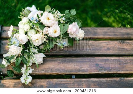 marriage, love, sentiment concept. on the wooden garden bench of chocolate colour there are flowers collected in bridal bouquet. with negative space for text