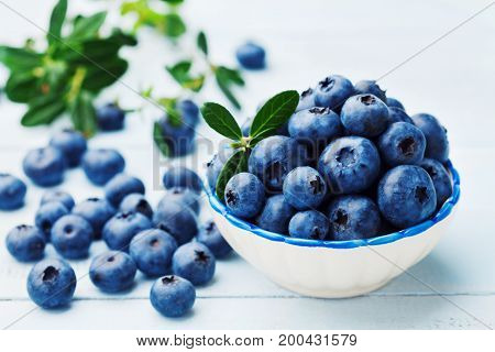Blueberry or great bilberry in bowl on blue rustic background. Organic superfood and healthy nutrition.