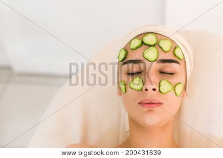Cucumber slices on eyes. Young woman with facial mask of cucumber in beauty salon. Girl with closed eyes with a mask of cucumbers on her face.