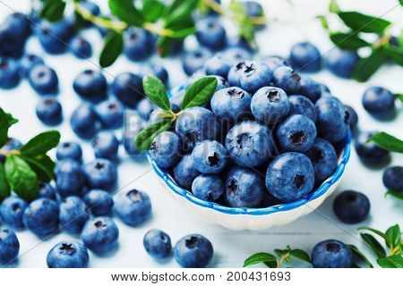 Crop of blueberry or great bilberry in bowl on blue wooden table. Organic superfood and healthy nutrition.