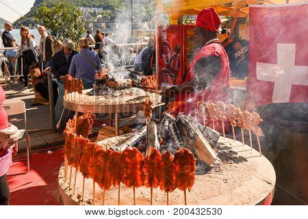 African Cook Preparing Grilled Meat Skewers At Street Food Festival