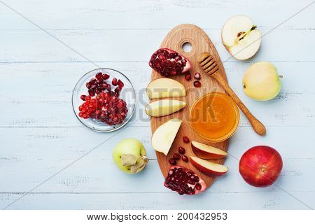 Honey apple slices and pomegranate serve on wooden kitchen board overhead view. Table set with traditional food for Jewish New Year Holiday Rosh Hashana.
