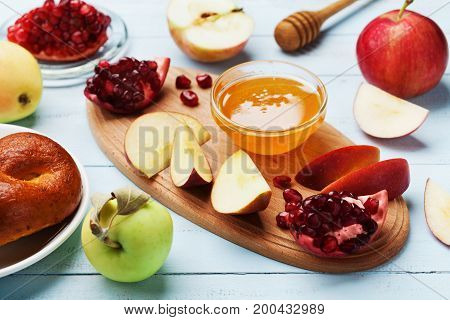 Honey apple slices pomegranate and hala serve on kitchen board. Table set with traditional food for Jewish New Year Holiday Rosh Hashana.