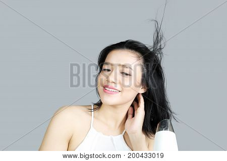 Portrait of young woman drying her hair with a hair dryer after bathing