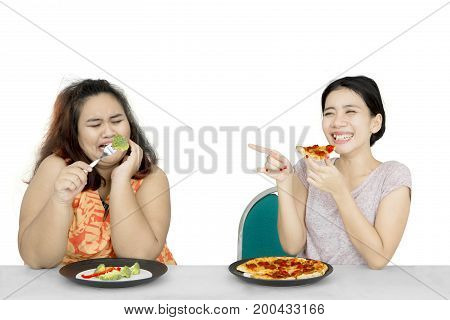 Lose weight concept. Young woman eating pizza while mocking her obese friend eat salad