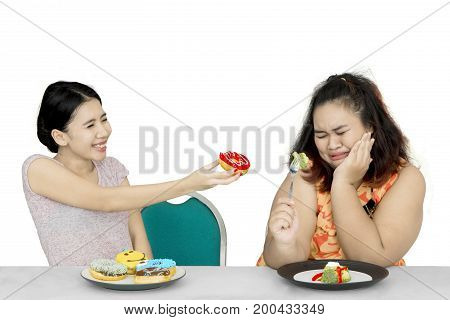 Lose weight concept. Young woman offers donuts to her overweight friend while eating salad
