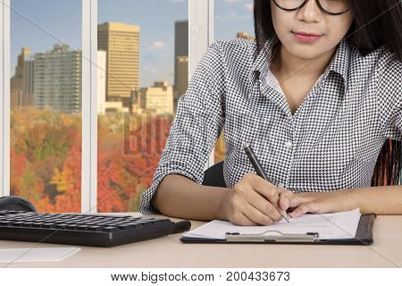 Close up of young businesswoman writing on paperwork while sitting in the office with autumn background on the window