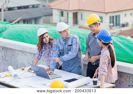 Harmonious Engineer And Technician Team Dicussing In Building Construction Site. Teamwork Collaborat